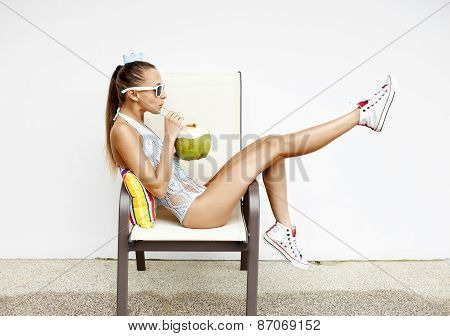 Fashion Young Woman  Drinking Coconut Water And Sitting On Chair