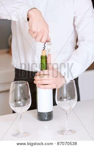Sommelier opens a wine bottle