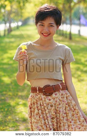 young beautiful woman wearing simply skirt clothes standing in park with yellow flowers in hand