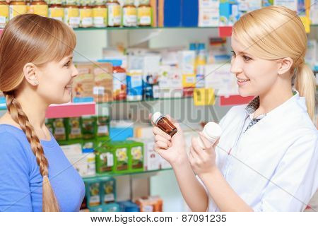 Pharmacist and a customer choosing medicine
