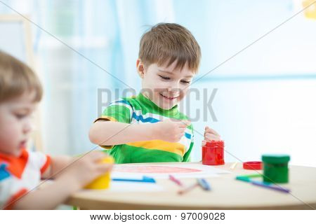 children painting in daycare or nursery or playschool
