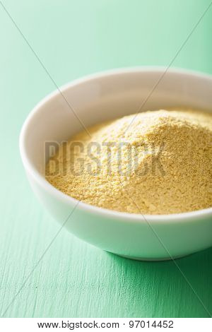 vegan nutritional yeast flakes in bowl poster