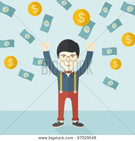 A young and cheerful chinese gentleman standing under falling raining money shower a coin and bill dollar money. Winner, happy concept. A contemporary style with pastel palette soft blue tinted