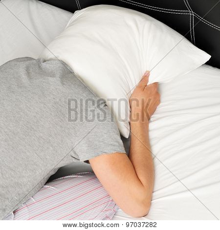 closeup of a young man face down in bed covering tightly his head with a pillow