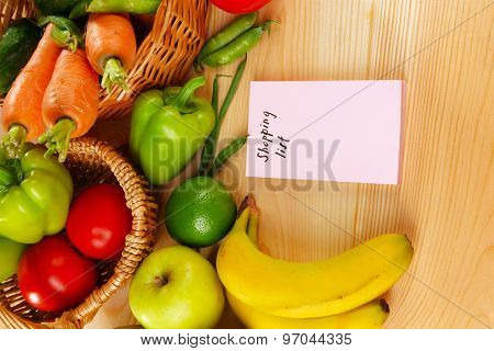 Shopping list wit fresh vegetables and fruits on wooden table, closeup poster