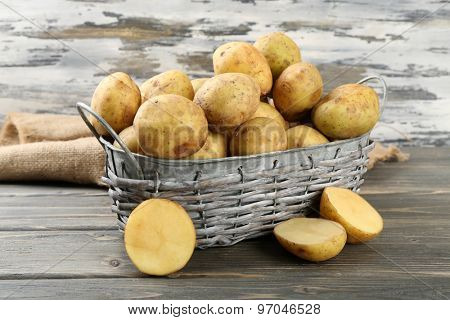 Young potatoes in wicker basket on wooden background