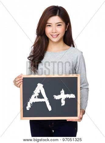 School girl hold with chalkboard and showing a A plus mark