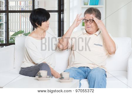 Asian old man headache, sitting on sofa with wife at home. Chinese family, senior retiree indoors living lifestyle.