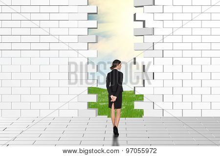 Beautiful businesswomen watching dilapidated brick wall