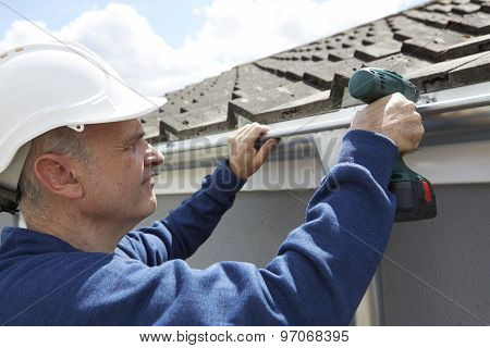 Workman Replacing Guttering On Exterior Of House