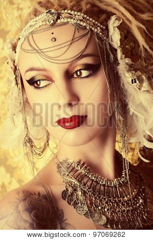 Close-up portrait of a magnificent traditional female dancer over golden vintage background. Ethnic dance. Belly dancing. Tribal dancing. Make-up, cosmetics.