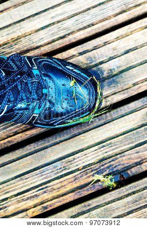Foot In Sneakers Standing On The Floor
