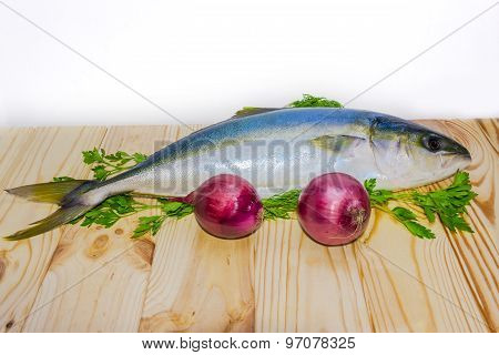 Whole Round Fish Yellowtail And Red Onion On A Wooden Surface