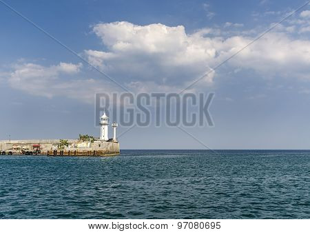 White lighthouse on the pier in the city of Yalta, Republic of Crimea, Russia