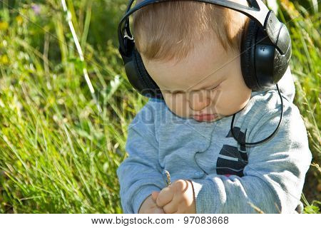 A little boy sitting in a meadow in the headphones. The day is bright and sunny. The kid looks at the grass.The child frowned and enthusiastically looking down. poster