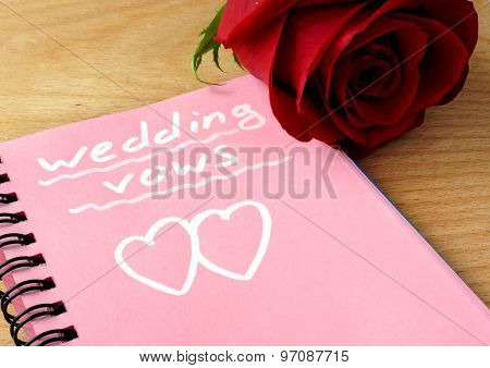 Pink notepad with wedding vows and rose.