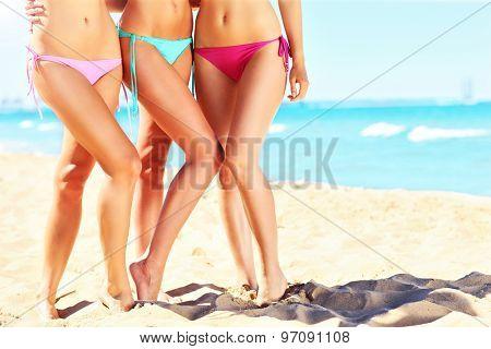 A picture of female legs in bikini on the beach
