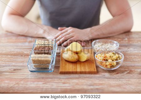 healthy eating, diet and people concept - close up of male hands with carbohydrate food on table