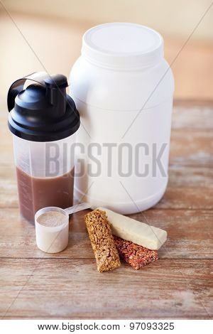 sport, fitness, diet and food concept - close up of jar, protein shake bottle and muesli bars on wooden table