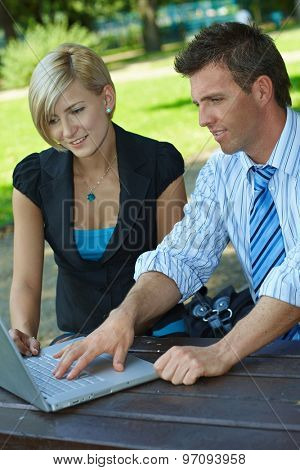 Blonde businesswoman and colleague working on laptop computer at outdoor park, sitting at a wooden table. Smiling, looking at screen.