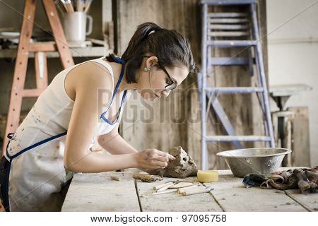young artist moulding raw clay in art studio poster