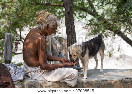 poor man and dog sits on the ghat along the Ganges river.