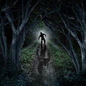Horror monster walking in a dark forest as a scary fantasy concept with a creepy thing coming out of a remote wilderness background with a moon glow behind it as a halloween fear symbol of haunted woods and panic anxiety. poster