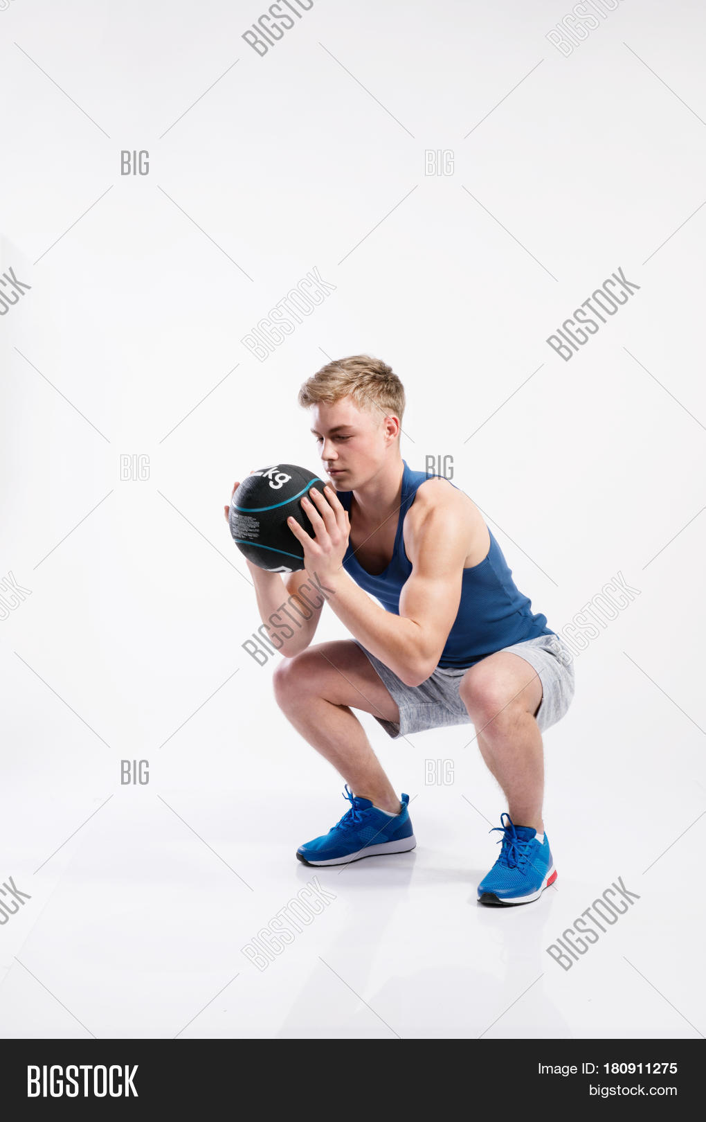 3e94f6600b678 Handsome hipster fitness man in blue tank top shirt and gray shorts holding  medicene ball