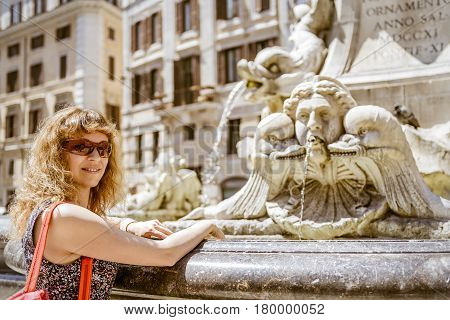 Young female tourist with baroque fountain in front of Pantheon at the Piazza della Rotonda in Rome, Italy