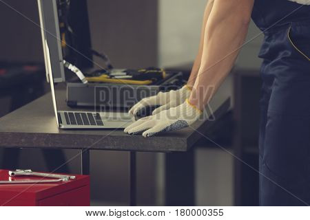 Auto mechanic working with laptop in car repair shop