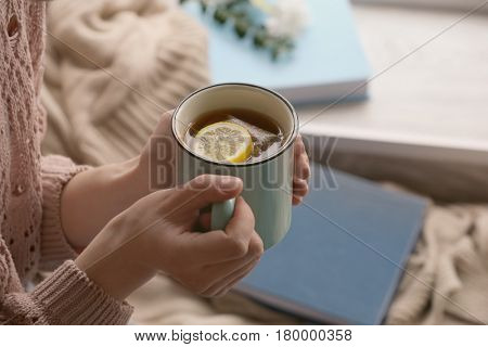 Young woman with cup of hot tea at home, closeup