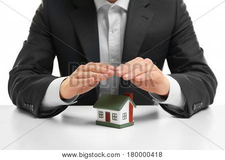 Insurance concept. Man covering with hands toy house on table