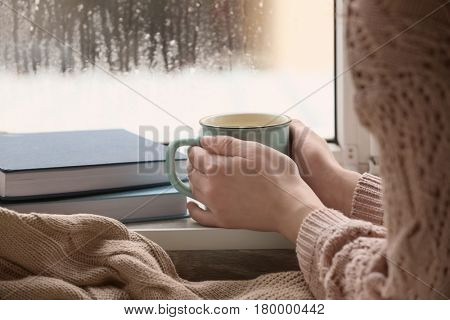Young woman with cup of hot tea near window, closeup