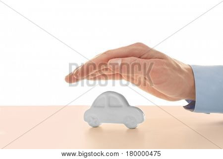 Insurance concept. Male hand over toy car on table