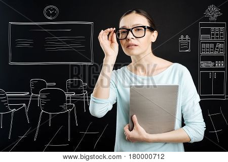 Switch on curiosity. Pleasant professional teahcer looking forward and holding textbook while working at school
