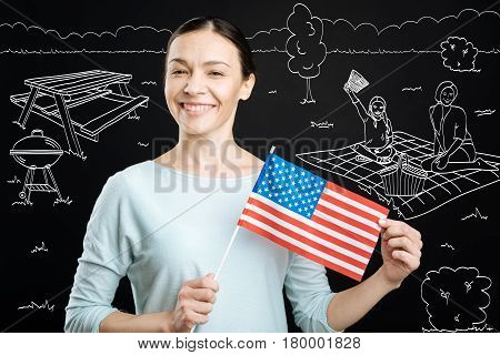 Proud citizen. Positive delighted woman holding american flag and celebrating independence day while enjoying picnic