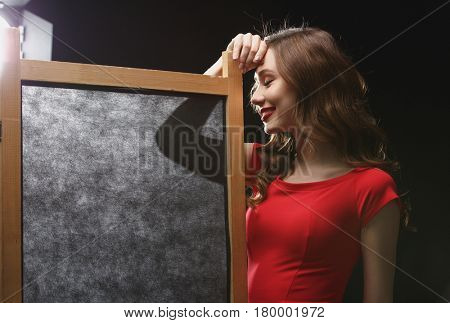 Smiling lovely young woman in red dress standing near folding screen over black background