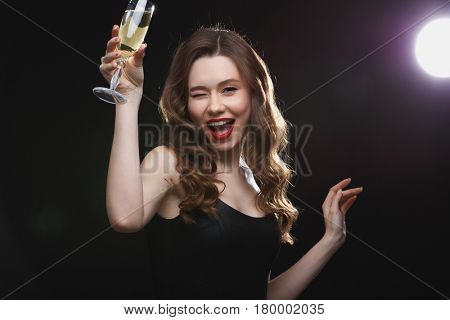 Cheerful beautiful young woman drinking champagne and winking