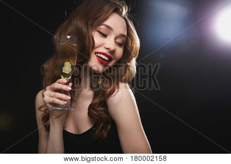 Cheerful gorgeous young woman with glass of champagne standing and smiling