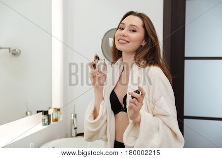 Cheerful attractive young woman standing and applying parfume in bathroom