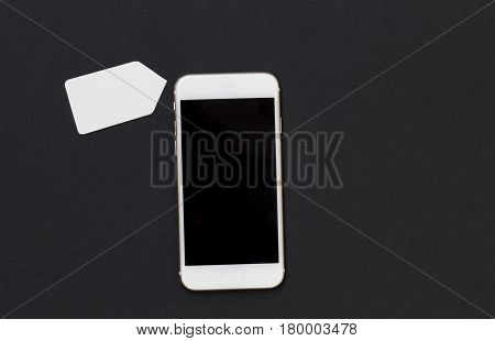 White phone with blank price tag. Smartphone and shopping label banner template. Black and white background with cellphone top view.