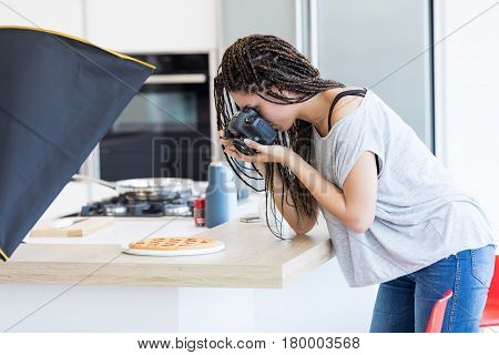 Side view of young woman with braids in grey T-shirt taking picture of a cake on wooden table surface in studio