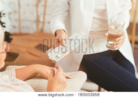 Consulting needy people . Friendly professional medical doctor sitting in the bedroom and helping pensioner while offering pills and glass of water