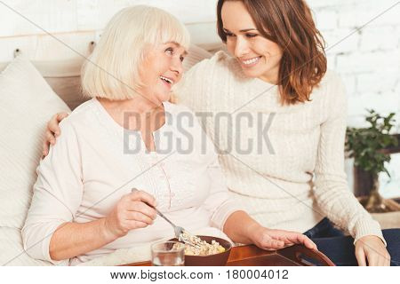 Taking care of my mom. Loving delightful young woman sitting at home and taking care of aged mother while offering breakfast to her
