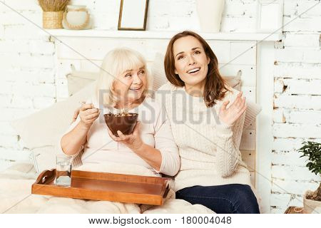 Discussing life with my grandmother. Thoughtful charming young woman sitting at home and taking care of retired grandmother while pensioner enjoying breakfast