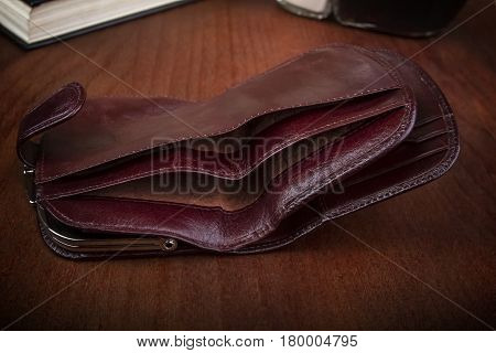 empty open men's wallet on a wooden background