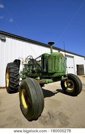Parts are stripped off  for salvage on an old green tractor.