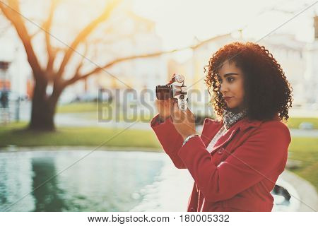 Serious pensive beautiful adult curly professional photographer in red trendy coat making photos using retro film camera near city pond on sunny day with copy space for your advertising text message