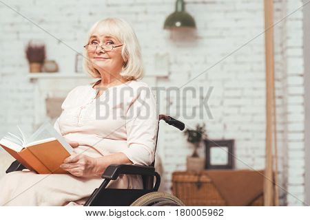 Cherishing my life . Aged thoughtful disabled woman sitting in the wheelchair at home while reading book and enjoying life