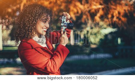 Beautiful smiling curly brunette Brazilian female photographer in red coat shooting photos using vintage film camera while standing in colorful park or forest with copy space area for your text